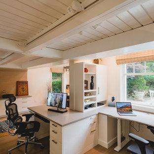 Modernes Arbeitszimmer mit weißer Wandfarbe, braunem Holzboden, Einbau-Schreibtisch, braunem Boden, freigelegten Dachbalken und Holzdielendecke in Boston