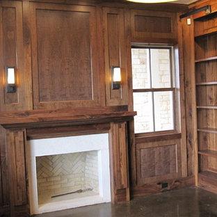 Imagen de despacho madera y madera, rústico, grande, madera, con paredes marrones, suelo de cemento, chimenea tradicional, marco de chimenea de ladrillo, escritorio empotrado, suelo marrón y madera