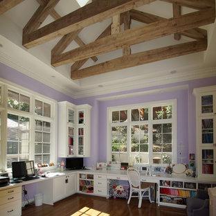 Aménagement d'un grand bureau atelier avec un mur violet, un sol en bois foncé et un bureau intégré.