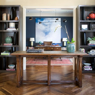 Home office - eclectic brown floor home office idea in Denver with blue walls