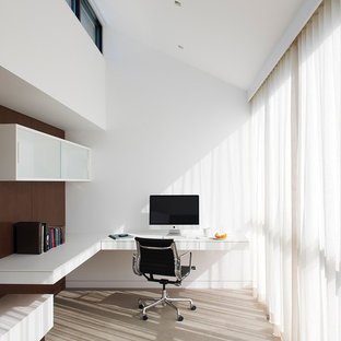 Example of a minimalist built-in desk study room design in New York with white walls