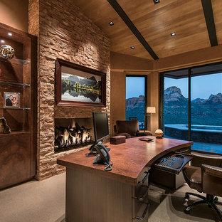 他の地域の大きいサンタフェスタイルのおしゃれな書斎 (茶色い壁、カーペット敷き、自立型机、標準型暖炉、石材の暖炉まわり) の写真