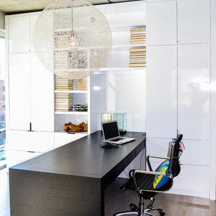 Foto de despacho urbano, de tamaño medio, sin chimenea, con escritorio empotrado, paredes blancas y suelo de madera clara