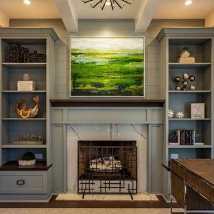 シャーロットの中くらいのトランジショナルスタイルのおしゃれな書斎 (グレーの壁、無垢フローリング、標準型暖炉、石材の暖炉まわり、自立型机、茶色い床) の写真