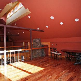 Cette image montre un grand bureau chalet avec un mur violet, un sol en bois brun, une cheminée standard, un manteau de cheminée en pierre et un bureau indépendant.