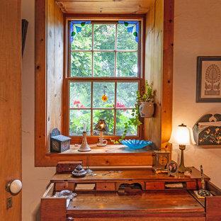 Modelo de despacho rústico, pequeño, sin chimenea, con paredes beige, suelo de madera clara, escritorio independiente y suelo marrón