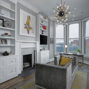 Стильный дизайн: кабинет в стиле современная классика с серыми стенами, темным паркетным полом, стандартным камином, фасадом камина из плитки, отдельно стоящим рабочим столом и коричневым полом - последний тренд