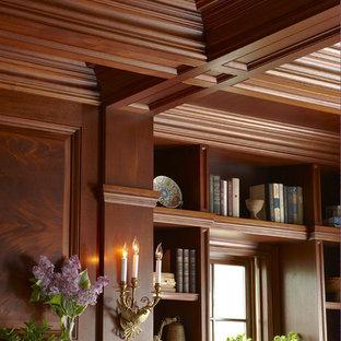 Idee per un ampio studio tradizionale con libreria, pareti marroni, parquet scuro, camino classico, cornice del camino in pietra e pavimento marrone