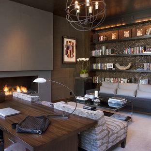 Ejemplo de despacho actual con moqueta, chimenea lineal y escritorio independiente