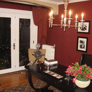 Idee per un piccolo ufficio chic con pareti rosse, pavimento in legno massello medio, nessun camino, scrivania autoportante e pavimento marrone