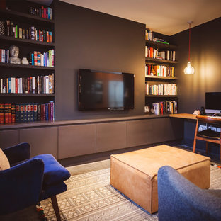 This is an example of a medium sized contemporary home office and library in London with a reading nook, purple walls, concrete flooring, no fireplace and a built-in desk.