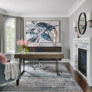 トロントの中サイズのトランジショナルスタイルのおしゃれな書斎 (グレーの壁、無垢フローリング、両方向型暖炉、石材の暖炉まわり、自立型机、茶色い床) の写真