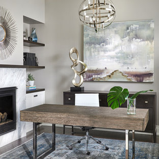 Klassisk inredning av ett mellanstort arbetsrum, med ett bibliotek, grå väggar, mörkt trägolv, en dubbelsidig öppen spis, en spiselkrans i sten, ett fristående skrivbord och brunt golv