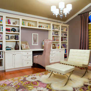 Foto de despacho actual, de tamaño medio, con paredes púrpuras, suelo de madera oscura, escritorio empotrado y suelo marrón