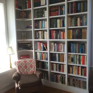 Foto på ett litet vintage arbetsrum, med ett bibliotek, beige väggar, mellanmörkt trägolv och brunt golv