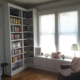 Inredning av ett klassiskt litet arbetsrum, med ett bibliotek, beige väggar, mellanmörkt trägolv och brunt golv