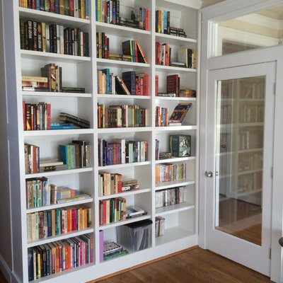 Home office library - small transitional medium tone wood floor and brown floor home office library idea in Charlotte with beige walls and no fireplace