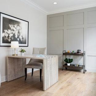 Пример оригинального дизайна: рабочее место среднего размера в стиле неоклассика (современная классика) с серыми стенами, светлым паркетным полом, отдельно стоящим рабочим столом, бежевым полом и панелями на части стены