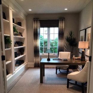 Пример оригинального дизайна: кабинет среднего размера в стиле модернизм с ковровым покрытием, отдельно стоящим рабочим столом, серыми стенами, библиотекой и серым полом без камина