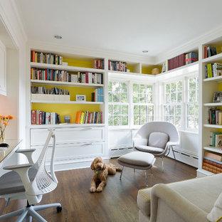 Foto di uno studio classico con scrivania incassata e pareti gialle