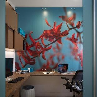 Idee per un piccolo ufficio minimal con pareti marroni, parquet chiaro, scrivania incassata e pavimento blu