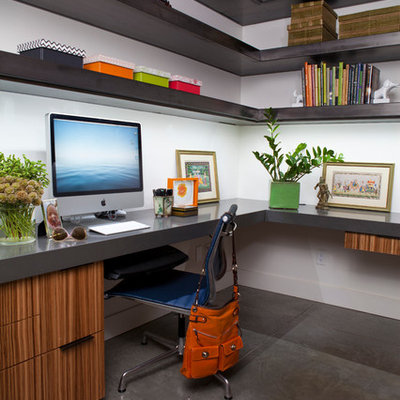 Example of a mid-sized trendy built-in desk concrete floor home office design in Other with white walls and no fireplace