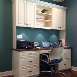 Inspiration för mellanstora klassiska hemmabibliotek, med blå väggar, mörkt trägolv, ett inbyggt skrivbord och brunt golv