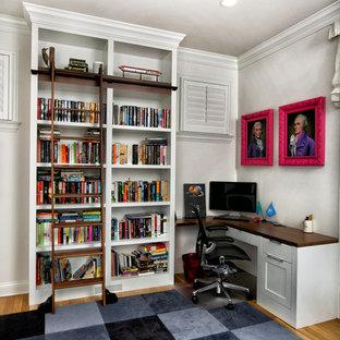 Foto di uno studio tradizionale con libreria, pareti bianche, parquet chiaro, scrivania incassata e pavimento giallo
