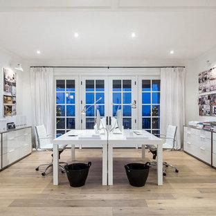 Example of a trendy freestanding desk light wood floor home studio design in Portland with white walls