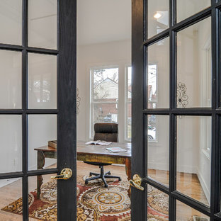 Example of an eclectic medium tone wood floor home office design in Nashville with white walls