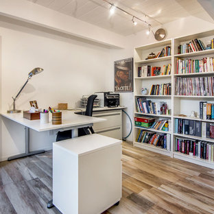 Mid-sized minimalist freestanding desk brown floor home office photo in San Francisco with white walls and no fireplace