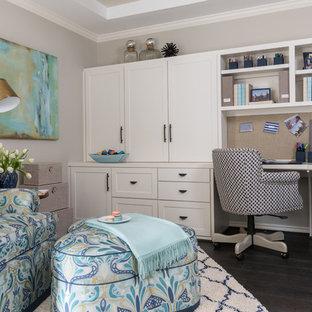 Imagen de sala de manualidades tradicional renovada, de tamaño medio, con paredes beige, suelo de madera oscura y escritorio empotrado