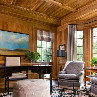 Esempio di un grande ufficio classico con pareti marroni, parquet scuro, camino classico, cornice del camino in pietra e scrivania autoportante