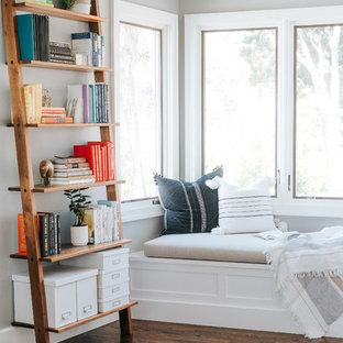 Foto på ett mellanstort vintage arbetsrum, med ett bibliotek, grå väggar, mellanmörkt trägolv, ett fristående skrivbord och brunt golv