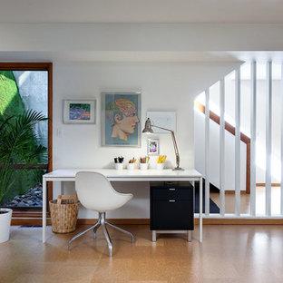 ポートランドの大きいコンテンポラリースタイルのおしゃれなホームオフィス・書斎 (白い壁、コルクフローリング、暖炉なし、自立型机) の写真