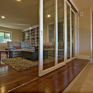 Immagine di uno studio minimal di medie dimensioni con libreria, pareti beige, pavimento in legno massello medio, scrivania incassata, pavimento marrone, camino classico e cornice del camino piastrellata