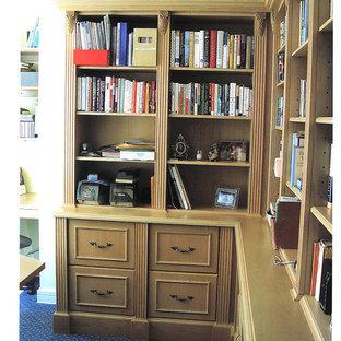 ニューヨークの中サイズのトラディショナルスタイルのおしゃれなホームオフィス・書斎 (ライブラリー、カーペット敷き、暖炉なし、ベージュの壁、造り付け机、青い床) の写真