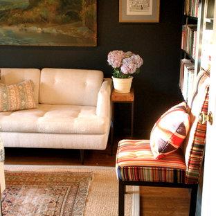 Foto på ett eklektiskt arbetsrum, med svarta väggar och mellanmörkt trägolv