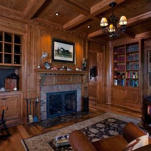Inspiration för ett stort lantligt arbetsrum, med ett bibliotek, bruna väggar, mellanmörkt trägolv, en standard öppen spis, en spiselkrans i tegelsten och ett fristående skrivbord