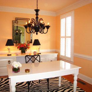 Modelo de despacho tradicional renovado con parades naranjas, suelo de madera oscura y escritorio independiente