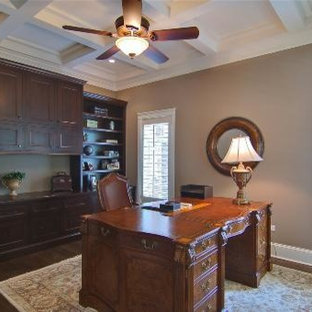 Idéer för ett stort klassiskt hemmabibliotek, med beige väggar, mellanmörkt trägolv, ett fristående skrivbord och brunt golv