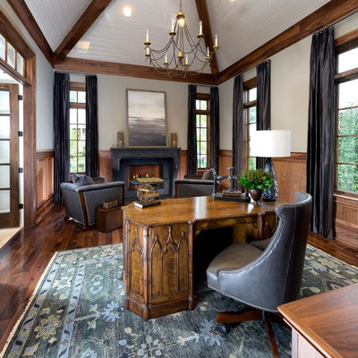 Inspiration for a mid-sized mediterranean freestanding desk dark wood floor and brown floor home office library remodel in Nashville with beige walls, a standard fireplace and a wood fireplace surround