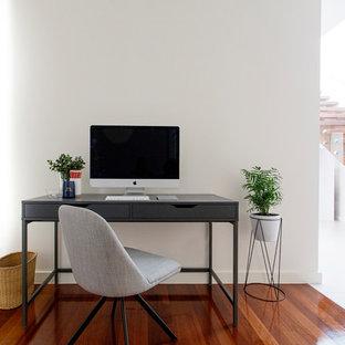 Cette photo montre un petit bureau tendance avec un mur blanc, un sol en bois brun, une cheminée standard et un manteau de cheminée en plâtre.