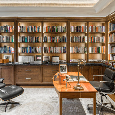Large elegant freestanding desk medium tone wood floor and brown floor home office library photo in Boston with gray walls and no fireplace
