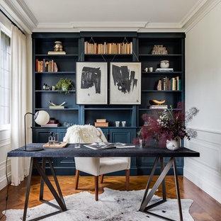 Mittelgroßes Klassisches Arbeitszimmer mit Arbeitsplatz, braunem Holzboden, freistehendem Schreibtisch, blauer Wandfarbe und braunem Boden in Boston
