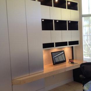 マイアミの中サイズのコンテンポラリースタイルのおしゃれなホームオフィス・仕事部屋 (ライブラリー、ベージュの壁、ライムストーンの床、造り付け机、ベージュの床) の写真