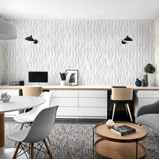 На фото: большое рабочее место в скандинавском стиле с белыми стенами, темным паркетным полом, встроенным рабочим столом и черным полом с