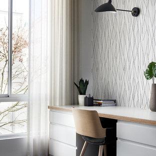 シドニーの大きい北欧スタイルのおしゃれな書斎 (白い壁、濃色無垢フローリング、造り付け机、黒い床) の写真
