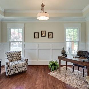 Esempio di uno studio tradizionale di medie dimensioni con pareti gialle, pavimento in legno massello medio, nessun camino, scrivania autoportante e pavimento marrone