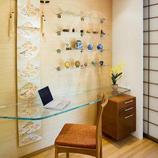 Built-in desk medium tone wood floor home office photo in San Francisco with beige walls